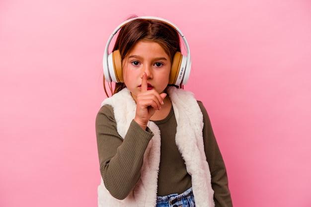 Weinig kaukasisch meisje het luisteren muziek die op roze wordt geïsoleerd die een geheim houdt of om stilte vraagt.