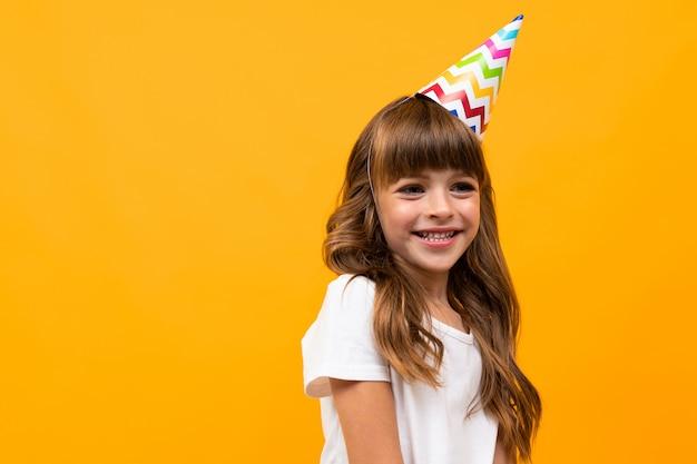 Weinig kaukasisch meisje met curlu bruin haar heeft verjaardagspartij die op wit wordt geïsoleerd