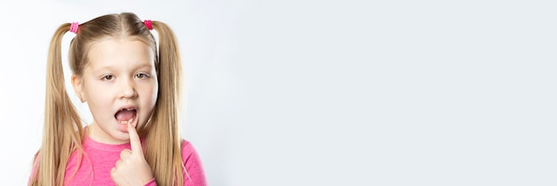 Weinig kaukasisch meisje met lang blond haar in roze kleren toont een melktand in haar mond die tegen een lichte achtergrond moet worden teruggetrokken. mondhygiëne concept.