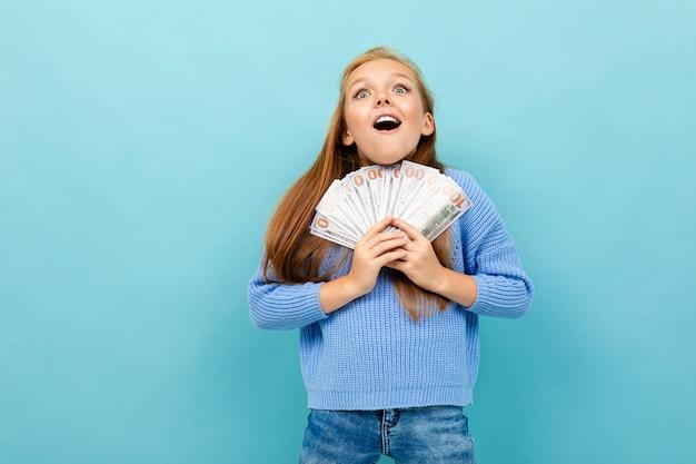 Weinig kaukasisch meisje met lang browhaar in blauwe hoody houdt heel wat geld dat op blauwe achtergrond wordt geïsoleerd
