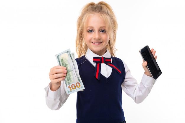Weinig kaukasisch schoolmeisje met blond haar koopt een telefoon en houdt geld