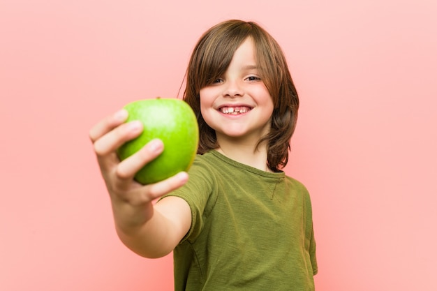 Weinig kaukasische jongen die een appel houdt