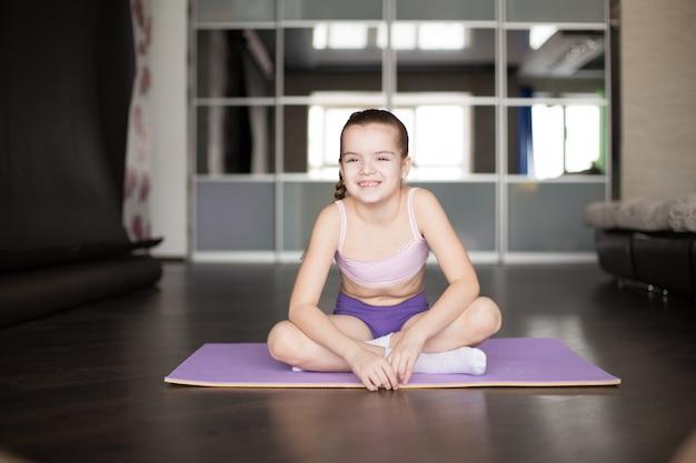 Weinig kaukasische meisjeszitting op mat in yoga stelt en mediterend.
