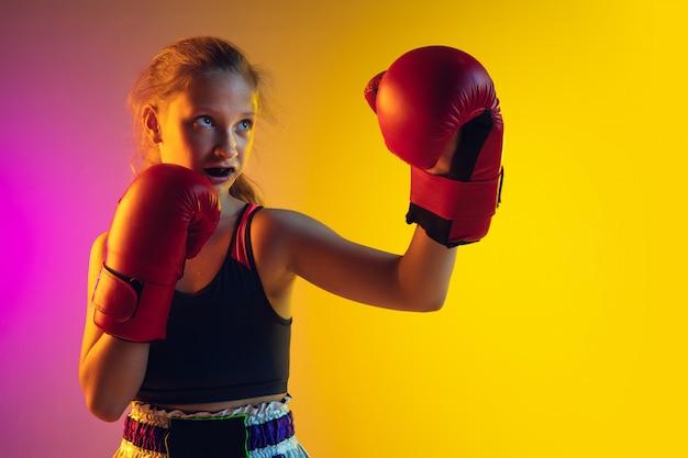 Weinig kaukasische vrouwelijke schopbokser opleiding op gradiëntachtergrond in neonlicht, actief en expressief