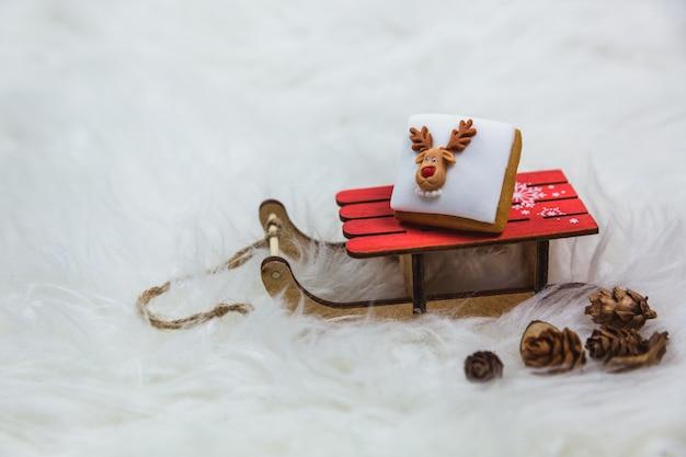Weinig kerstmiskoekje op een kleine houten slee op lichten. vrolijk kerstfeest, poster of briefkaart.