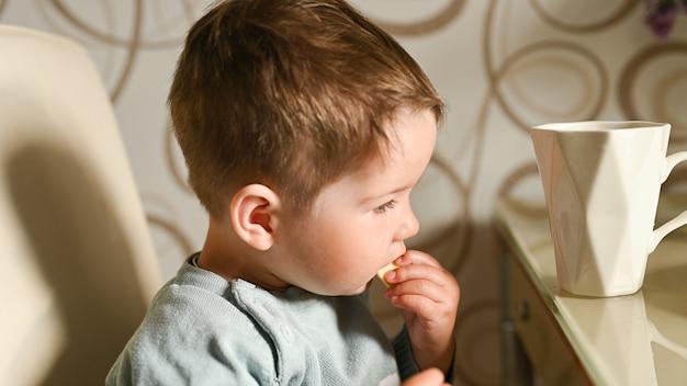 Weinig kind drinkt zelf water uit een mok. onafhankelijke baby