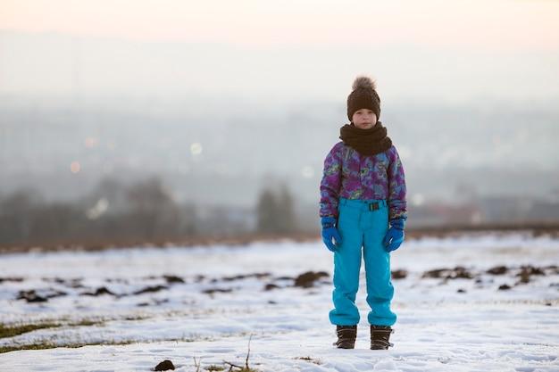 Weinig kindjongen die zich buiten alleen op de winter met sneeuw bedekt.