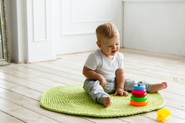 Weinig kindjongen plaing met stuk speelgoed piramide op gebreid carpeet op de houten vloer binnen