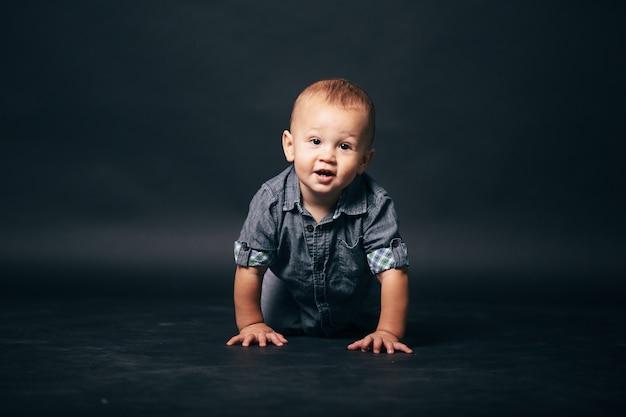 Weinig kindjongen van één jaar in denimoutfit op een grijze studioachtergrond. schattige baby lacht.