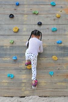 Weinig kindmeisje die bij het vrije beklimmen op de speelplaats houten muur in openlucht proberen.