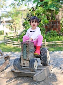 Weinig kindmeisje die op een oude houten stuk speelgoed tractor in de tuin berijden.
