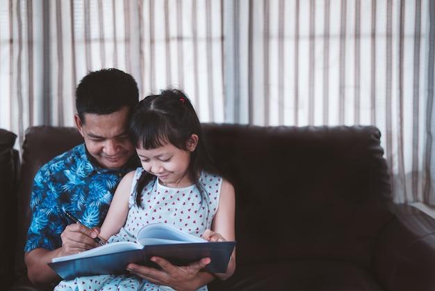 Weinig kindmeisje en vader genieten samen thuis van leesboek. sociale afstand tijdens quarantaine, online onderwijsconcept
