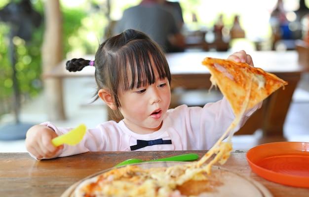 Weinig kindmeisje geniet van etend pizza.