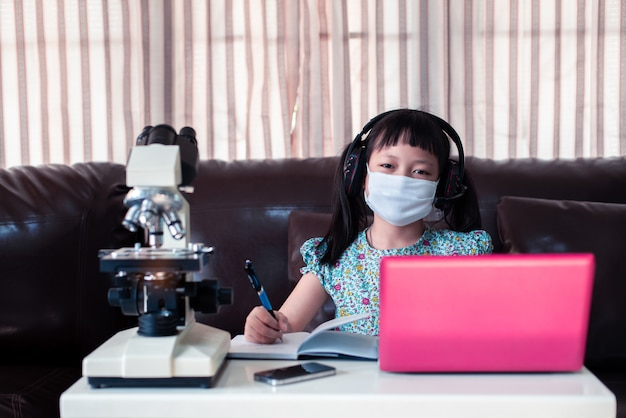 Weinig kindmeisje gezichtsmasker dragen en hoofdtelefoons die online door laptop en microscoop thuis, afstandsonderwijs leren te gebruiken