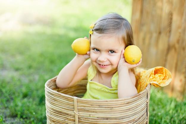 Weinig kindmeisje met citroenen bij limonadetribune in park. portret van grappige baby in mand met fruit