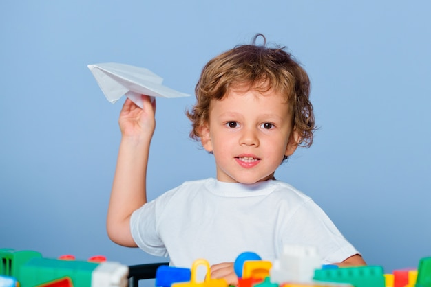 Weinig klaar om te studeren. kinderschool. kleine jongen leerling met blije gezichtsuitdrukking houdt papieren vliegtuigje lachend en glimlachend vast.