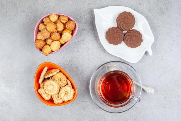 Weinig koekjes op bord naast kommen koekjeschips en een kopje thee op marmeren oppervlak.