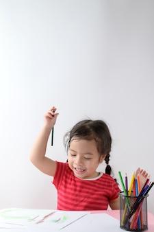 Weinig krullend aziatisch meisje geniet van thuis trekkend. onderwijs concept.