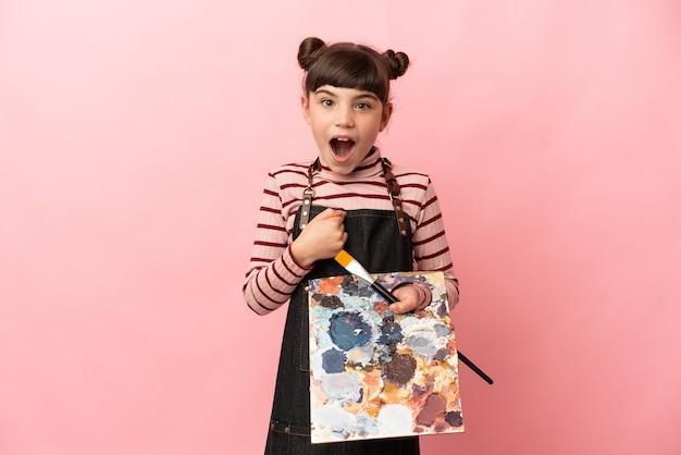 Weinig kunstenaarsmeisje dat een palet houdt dat op roze muur met verrassingsgelaatsuitdrukking wordt geïsoleerd