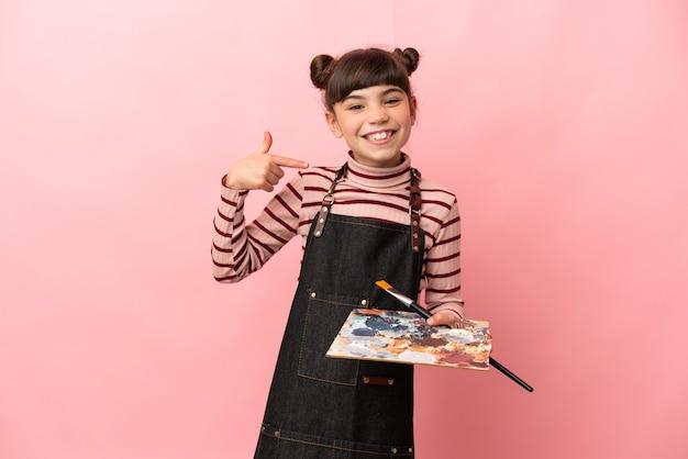 Weinig kunstenaarsmeisje dat een palet houdt dat op roze muur wordt geïsoleerd die een duim omhoog gebaar geeft