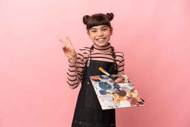 Weinig kunstenaarsmeisje dat een palet houdt dat op roze muur wordt geïsoleerd die en overwinningsteken glimlacht toont