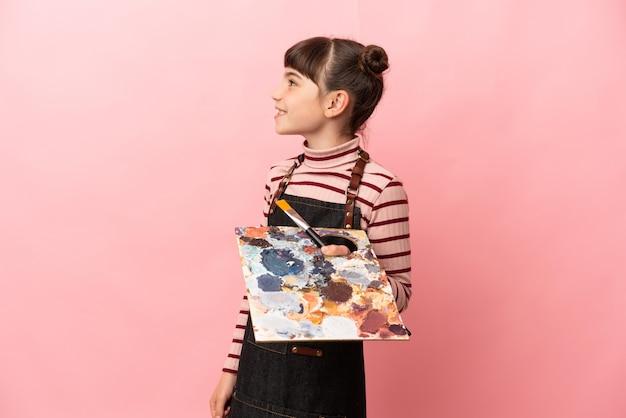 Weinig kunstenaarsmeisje dat een palet houdt dat op roze muur wordt geïsoleerd die kant kijkt