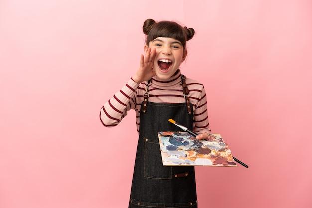 Weinig kunstenaarsmeisje dat een palet houdt dat op roze muur wordt geïsoleerd die met wijd open mond schreeuwt