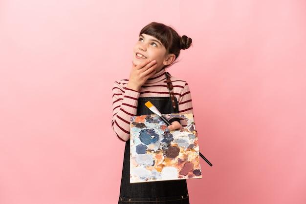 Weinig kunstenaarsmeisje dat een palet houdt dat op roze muur wordt geïsoleerd die omhoog kijkt terwijl het glimlachen