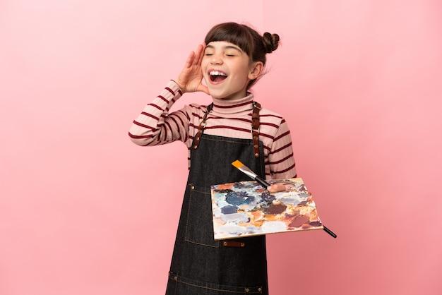Weinig kunstenaarsmeisje dat een palet houdt dat op roze muur wordt geïsoleerd die veel glimlacht