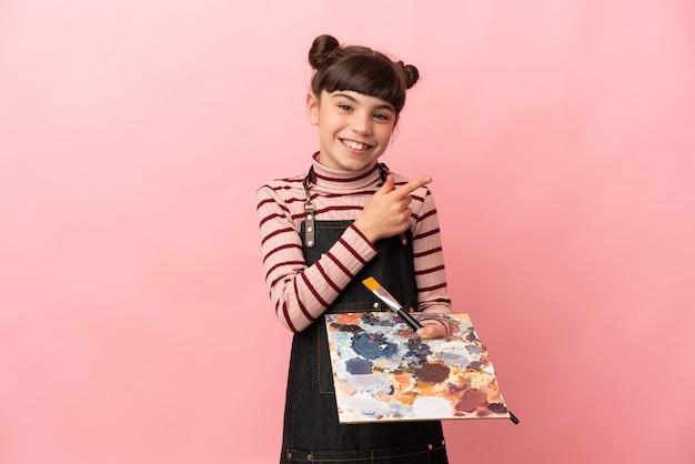 Weinig kunstenaarsmeisje dat een palet houdt dat op roze muur wordt geïsoleerd die vinger aan de kant richt