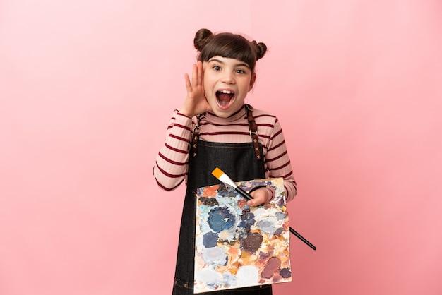 Weinig kunstenaarsmeisje dat een palet houdt dat op roze muur wordt geïsoleerd met verbazing en geschokte gelaatsuitdrukking