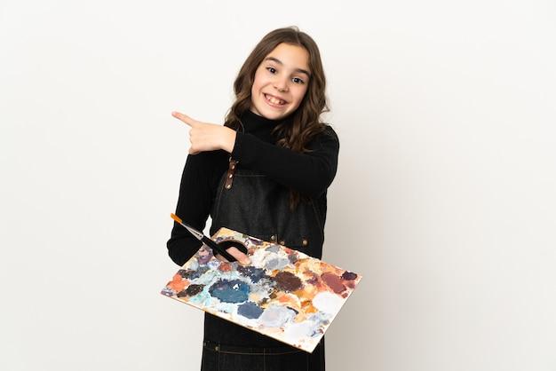 Weinig kunstenaarsmeisje dat een palet houdt dat op witte achtergrond wordt geïsoleerd die terug richt