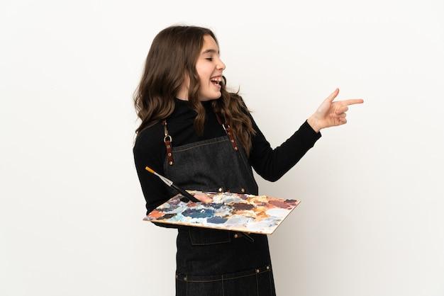 Weinig kunstenaarsmeisje dat een palet houdt dat op witte achtergrond wordt geïsoleerd die vinger naar de kant richt en een product voorstelt