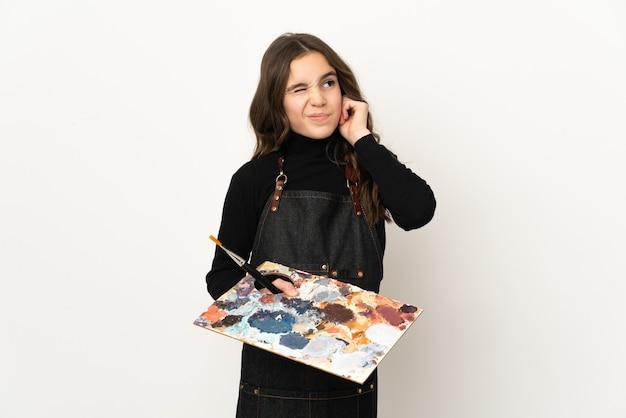 Weinig kunstenaarsmeisje dat een palet houdt dat op witte gefrustreerde muur wordt geïsoleerd en oren behandelt