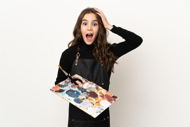 Weinig kunstenaarsmeisje dat een palet houdt dat op witte muur met verrassingsuitdrukking wordt geïsoleerd