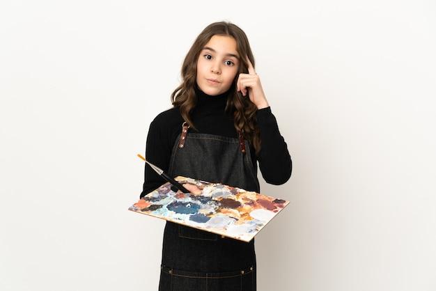 Weinig kunstenaarsmeisje dat een palet houdt dat op witte muur wordt geïsoleerd die een idee denkt