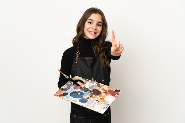 Weinig kunstenaarsmeisje dat een palet houdt dat op witte muur wordt geïsoleerd die en een vinger toont opheft