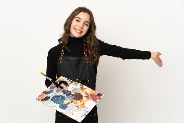Weinig kunstenaarsmeisje dat een palet houdt dat op witte muur wordt geïsoleerd die handen naar de kant uitbreidt om uit te nodigen om te komen