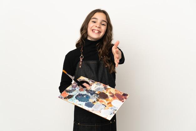 Weinig kunstenaarsmeisje dat een palet houdt dat op witte muur wordt geïsoleerd die handen schudt voor het sluiten van een goede deal
