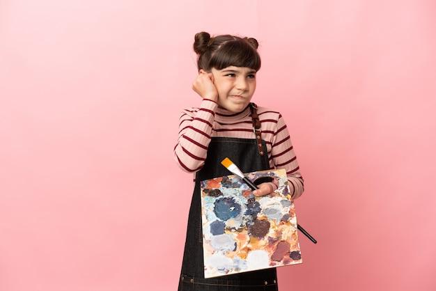 Weinig kunstenaarsmeisje die een palet houden dat op roze gefrustreerde muur wordt geïsoleerd en oren behandelt