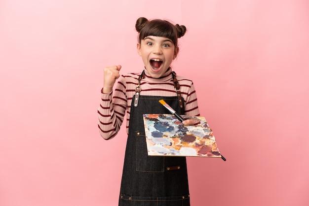 Weinig kunstenaarsmeisje die een palet houden dat op roze muur wordt geïsoleerd die een overwinning in winnaarspositie viert