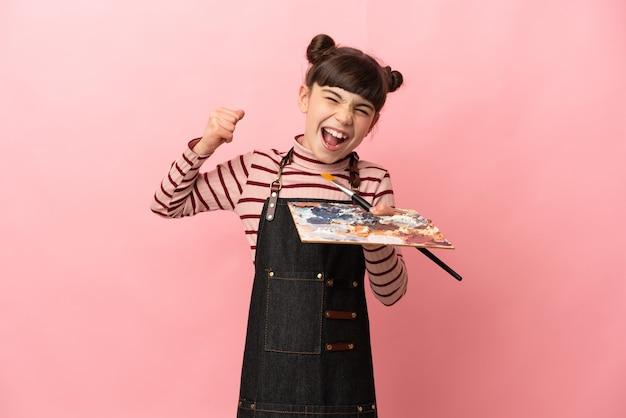 Weinig kunstenaarsmeisje die een palet houden dat op roze muur wordt geïsoleerd die een overwinning viert