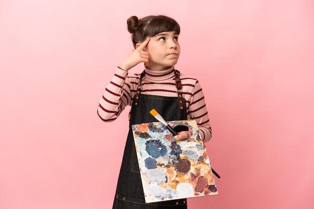 Weinig kunstenaarsmeisje die een palet houden dat op roze muur wordt geïsoleerd die twijfelt en denkt