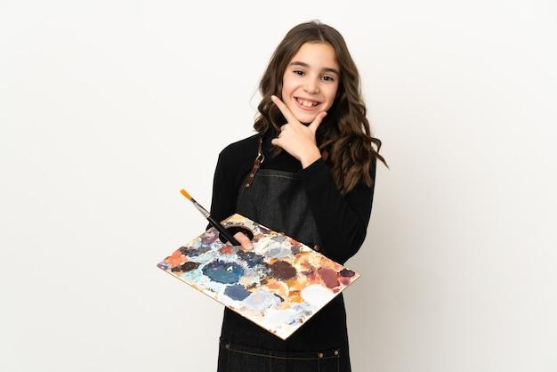 Weinig kunstenaarsmeisje die een palet houden dat op witte gelukkig en gelukkige muur wordt geïsoleerdm