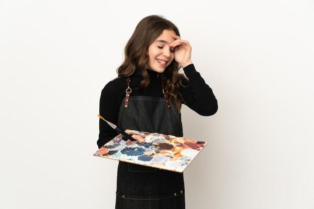 Weinig kunstenaarsmeisje die een palet houden dat op witte muur het lachen wordt geïsoleerd