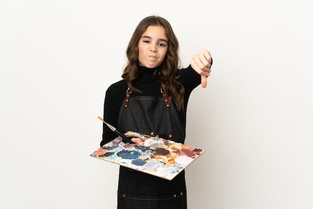 Weinig kunstenaarsmeisje die een palet houden dat op witte muur wordt geïsoleerd die duim met negatieve uitdrukking toont