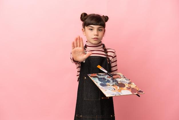 Weinig kunstenaarsmeisje die een palet op roze houden stopgebaar maken