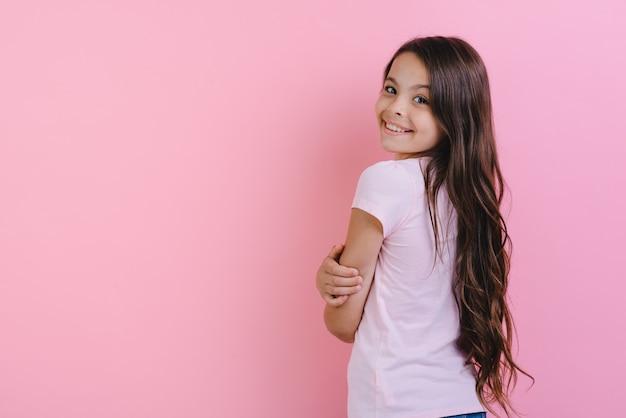 Weinig langharig meisje die achteruitgaan, die zijn hoofd draaien naar de camera over roze