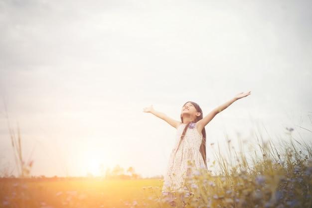 Weinig leuk aziatisch meisje dat zich onder de paarse bloem veld su
