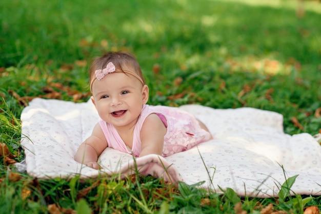 Weinig leuk babymeisje dat op een witte plaid op het gras in het park ligt.